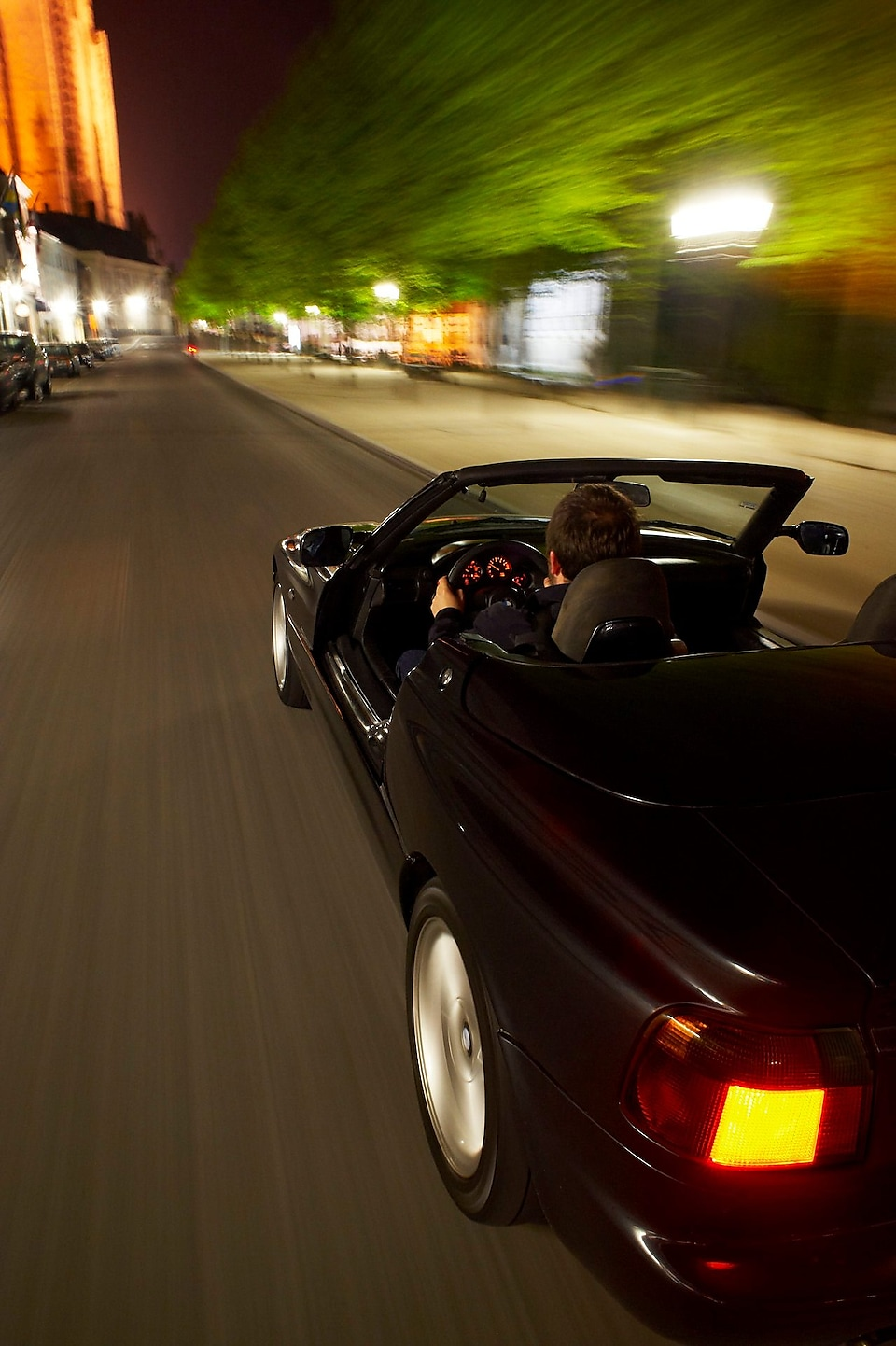 Black convertible car driving through Brugge streets at night